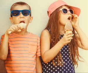 Boy and girl eating ice cream cones with sunglasses on.